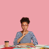 Vertical indoor shot of secret woman dressed in casual striped clothes, makes hush gesture, sits at desktop, surrounded with crayons, models against pink background, free space for your advertisement - 232730958