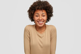 Smiling dark skinned woman has Afro hairstyle, shows white perfect teeth, glad to recieve good mark on exam, wears beige sweater, models against studio background. Ethnicity and emotions concept - 232730962