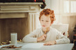 Need to think. Serious red haired child pressing lips while looking aside and going to write letter