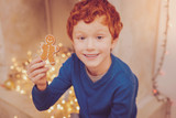 Favorite dessert. Charming red-haired man sitting near the chimney and showing a gingerbread man to the camera while smiling - 232732122