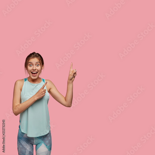 Leinwandbild Motiv Content slim woman dressed in sportswear, stands on left side, indicates upwards, shows free space against pink background, being impressed by something positive. Advert, feminity, lifestyle