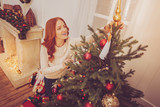 Last fine detail. Beautiful ginger-haired young woman standing near Christmas tree and putting a topper on it while smiling happily - 232732768
