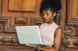African American Businesswoman working in New York. Young beautiful black woman with afro hairstyle wearing sleeveless light color top, looking down, working on laptop computer by vintage office door.