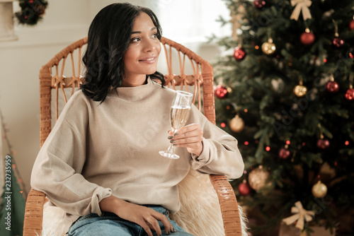 Poster Great drink. Nice attractive dreamy woman sitting in the chair and holding a glass while having champagne