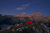 Red tent on the mountain peak during sunrise
