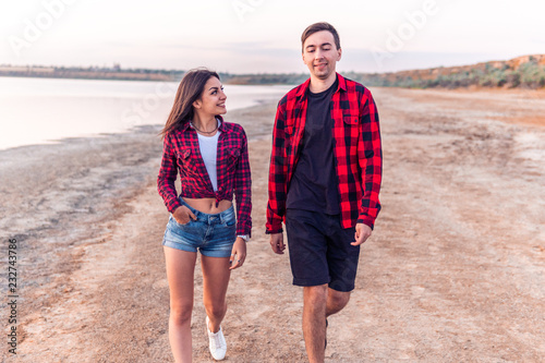 Happy young couple on the beach walking together during sunset. Date outdoors. They look happy
