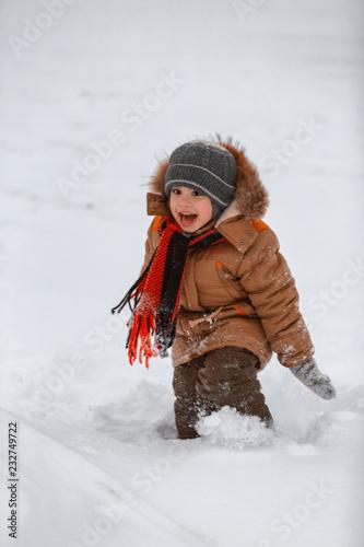 Foto Murales little boy having fun in the snow