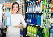 Leinwanddruck Bild - friendly girl customer looking for cleaners for home in supermarket