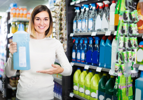 Leinwanddruck Bild friendly girl customer looking for cleaners for home in supermarket