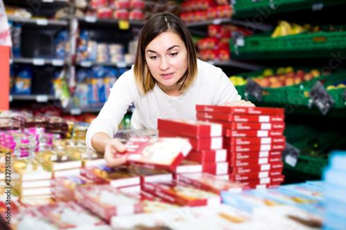 Leinwanddruck Bild Woman choosing delicious sweets