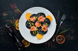 Black ravioli with salmon and parmesan cheese. In a plate on a wooden background. Top view. Free copy space.