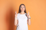 Young woman in basic clothing throws dab isolated on yellow background. - 232758146