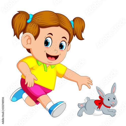 fototapeta na ścianę Little girl catch up a rabbit
