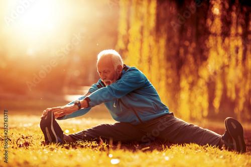 Foto Murales Senior man stretching in the park