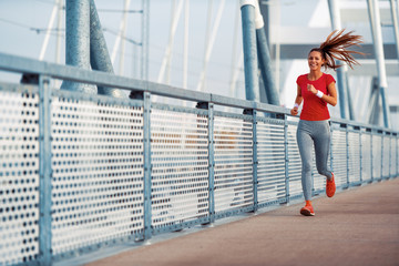 Young fitness woman running in the city