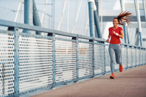 Wall mural Young fitness woman running in the city