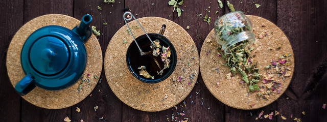 a small blue teapot, a mug of tea and dry herbal tea on a wooden background. Herbal medicine. tea from flowers. © ritiniya
