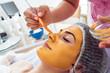 Leinwandbild Motiv Facial cosmetic procedure in spa salon. The procedure for applying a mask to the face of a beautiful woman