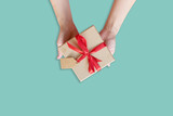 top view hand woman holding brown gift box for new year on green pastel color background with space. - 232775597