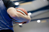 A referee holds a basketball during a basketball game. Judge a match