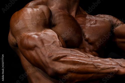 Zakończenie ręki sprawności fizycznej władza. Silny i przystojny kulturysta demonstruje swoje mięśnie i biceps