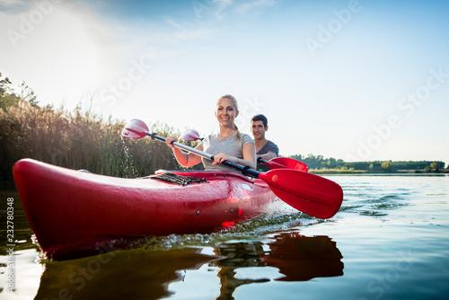 Leinwanddruck Bild Happy couple rowing kayak on lake