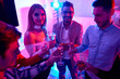 Group of young men and women having champagne in glasses gathering on house party for New Year