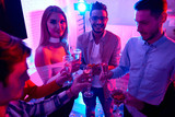 Group of young men and women having champagne in glasses gathering on house party for New Year  - 232782748