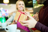 Portrait of adult couple exchanging presents at table in cafe, focus on unrecognizable holding gift box, copy space - 232788930