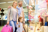 Portrait of happy family looking at window displays while shopping in mall together, copy space - 232789522