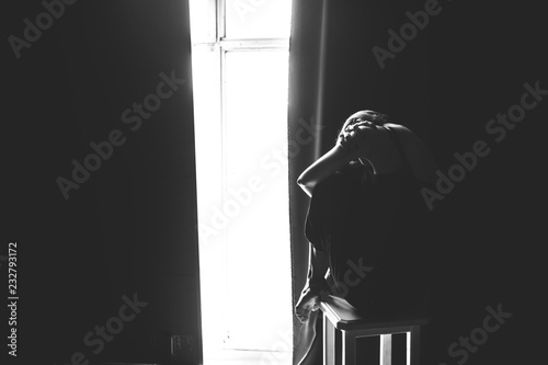 The social theme female loneliness pain suffering. Abastration male violence family. A young beautiful Caucasian woman in black clothes sitting on three chairs in large dark room. Srach and despair - 232793172