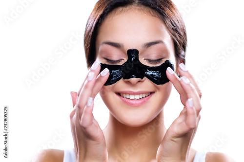 Leinwanddruck Bild Beautiful woman applying coal mask