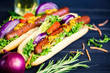 delicious hot dog with vegetables and sausage on a black background - 232807372