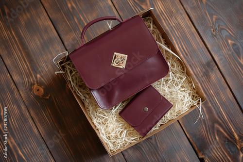 Prezenta pudełko z rzemienną torbą i kiesą na ciemnym drewnianym tle. Może być używany jako tło