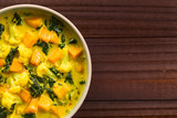 Homemade Indian vegetarian cauliflower pumpkin and spinach curry in bowl, photographed overhead with copy space on the side (Selective Focus, Focus on the dish)