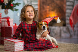 girl child celebrates Christmas with dog Jack Russell Terrier at home under the Christmas tree