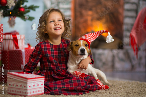 girl child celebrates Christmas with dog Jack Russell Terrier at home under the Christmas tree © Anatoly Tiplyashin