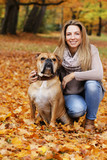 Middle age woman with her dog enjoying the autumnal nature