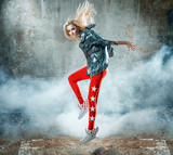 Pretty blond lady dancing in a grungy place full of smoke