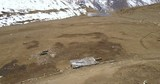 Aerial drone elevating, advancing over chorten in dry high alititude landscape near Ice Lake above 4000m elevation revealing Himalayan mountain range above Manang village, Nepal. 4k 1.9:1 23.976fps - 232844127
