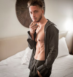 Sexy male model standing alone on bed in his bedroom, looking at camera with a seductive attitude,, with shirt open on muscular chest and torso - 232844303