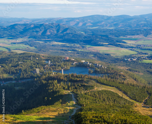 Aerial view on Strbske pleso village and blue mountain lake from chata pod soliskom with forest, hills aHigh Tatra mountains, Slovakia, summer golden hour © Kristyna