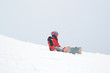 A small child fell off a snowboard