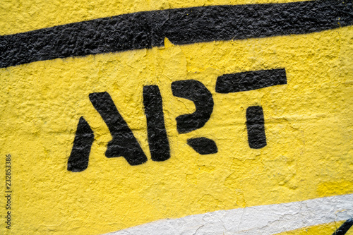 """Fragment of graffiti drawing. Word """"art"""" in black on yellow old wall decorated with paint in street art style."""