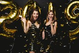 Beautiful Women Celebrating New Year. Happy Gorgeous Girls In Stylish Sexy Party Dresses Holding Gold 2019 Balloons, Having Fun At New Year's Eve Party. Holiday Celebration. High Quality Image - 232868594