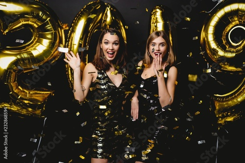 Foto Murales Beautiful Women Celebrating New Year. Happy Gorgeous Girls In Stylish Sexy Party Dresses Holding Gold 2019 Balloons, Having Fun At New Year's Eve Party. Holiday Celebration. High Quality Image