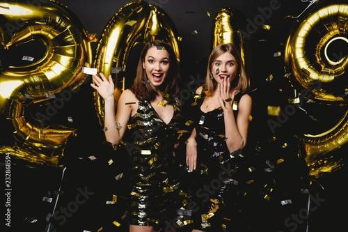 Piękne kobiety świętuje nowy rok. Szczęśliwe Wspaniałe Dziewczyny W Stylowej Sexy Sukienek Trzymających Złoto 2019 Balonów, Zabawy Na Imprezę Noworoczną. Świąteczne świętowanie. Obraz wysokiej jakości