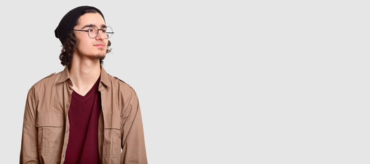 Horizontal shot of pensive young hipster looks pensively aside, wears round spectacles, casual clothes, isolated over white background with free space for your advertising content or promotion © sementsova321