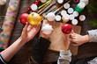 High angle close up of kids holding Christmas baubles over wooden table in crafting class, copy space