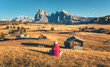 Sitting woman on the hill looking in meadows and mountains at sunset in autumn. Alpe di Siusi, Dolomites, Italy. Landscape with girl in red jacket, field with yellow grass, wooden houses and rocks